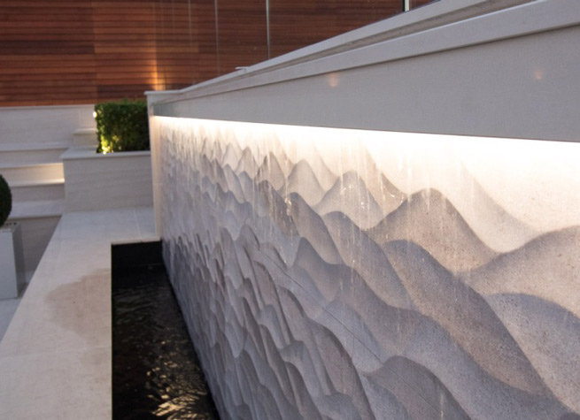 bespoke contemporary poolside waterfall feature