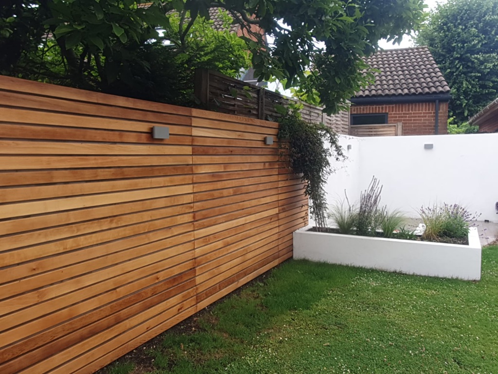 garden with lateral timber fence and white accented walls
